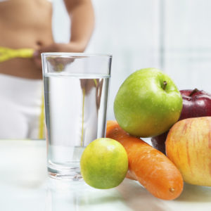 Fruit and water on table with female body on sport attire at background measuring h er stomach. shot for diet concept